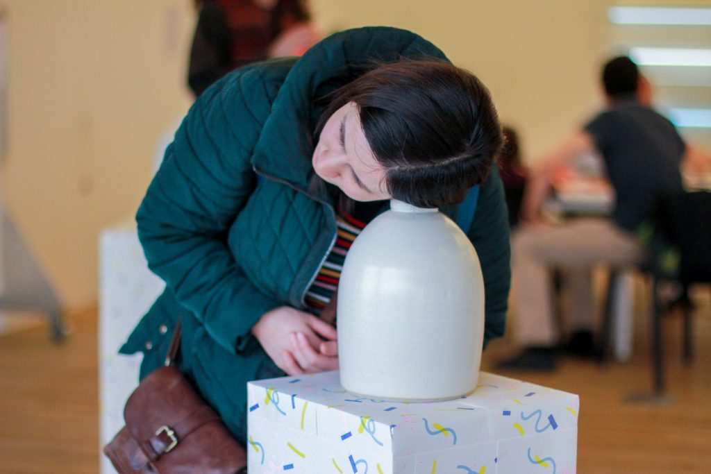 A photograph of a person leaning their ear towards an object on a plinth. The person has dark brown hair and is wearing a green puffer jacket and has a brown leather bag. The object is white, round and looks like a vase. The top part of the plinth is visible and it has various squiggly yellow, blue and green lines on it. The background is out of focus and shows a person sitting at a table on the right side of the photograph.