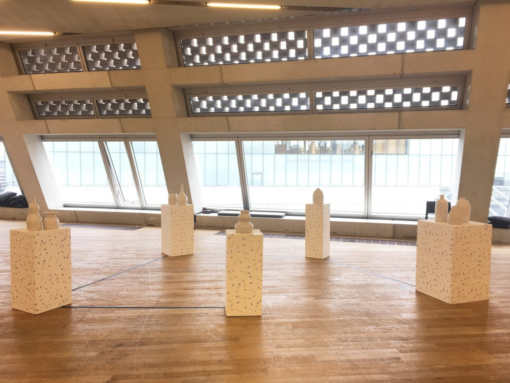 A photograph of a large room with five plinths and objects on them. The room has high ceilings, a wooden floor and large windows letting a lot of light in. The white plinths appear to have a speckled pattern on them in a darker colour. On top of the plinths there are different white vase-shaped objects.