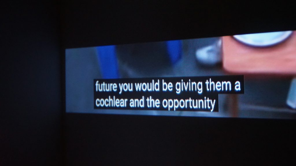 """An image of a rectangular screen. The screen is much longer than it is high. On the screen, there are white subtitles with a black box around them that say """"future you would be giving them a cochlear and the opportunity"""". Behind the subtitles, a few blurred shapes can be seen which appear to be a table and shoe. The screen is within a black environment which surrounds it."""