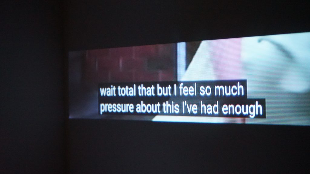 """An image of a rectangular screen. The screen is much longer than it is high. On the screen, there are white subtitles with a black box around them that say """"wait total that but I feel so much pressure about this I've had enough"""". Behind the subtitles, a few blurred shapes can be seen but it is uncertain what they are. The left side is brown and could be brick, the right shows a white shape. The screen is within a black environment which surrounds it."""