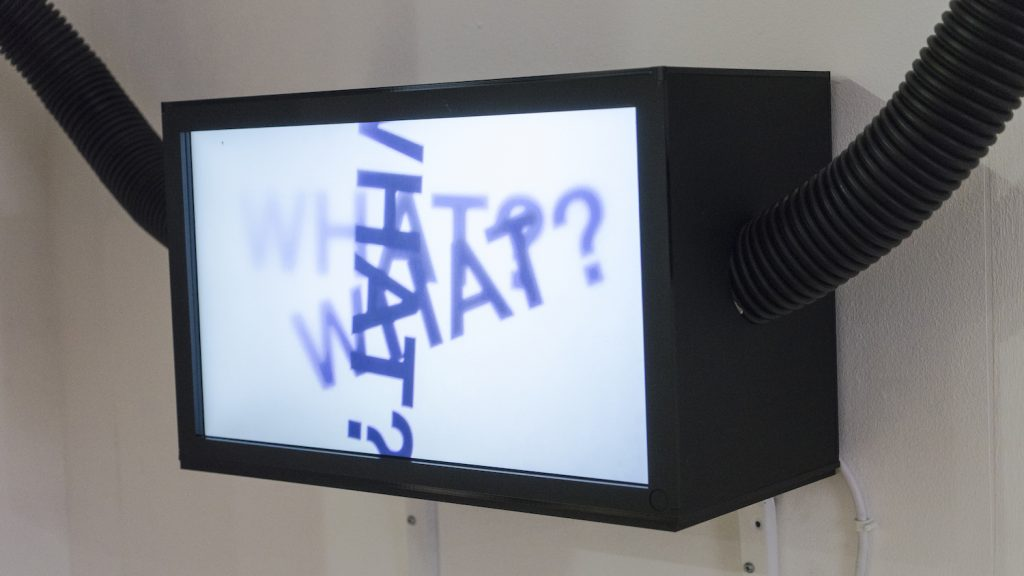 A photograph of a television facing forwards and slightly to the left. The television is a black box shape and mounted to a white wall. Coming out from the left and right side of the television are two black tubes. On the screen, the fading words 'WHAT?' are repeated three times overlapping on top of each other at different angles.